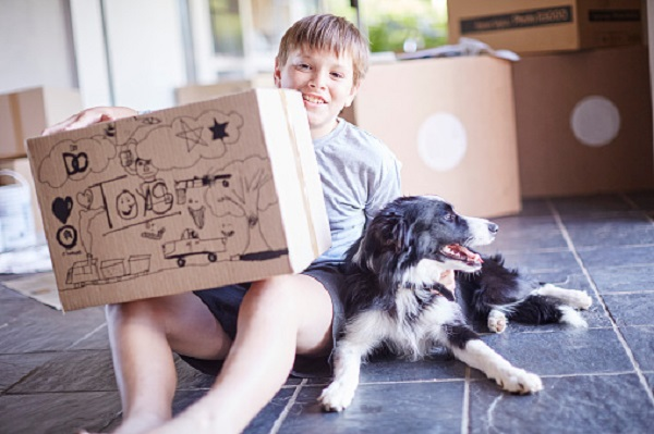Boy sitting with his dog and boxes in new home
